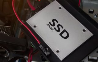 SSD drive laying on computer case with cables & mounts.